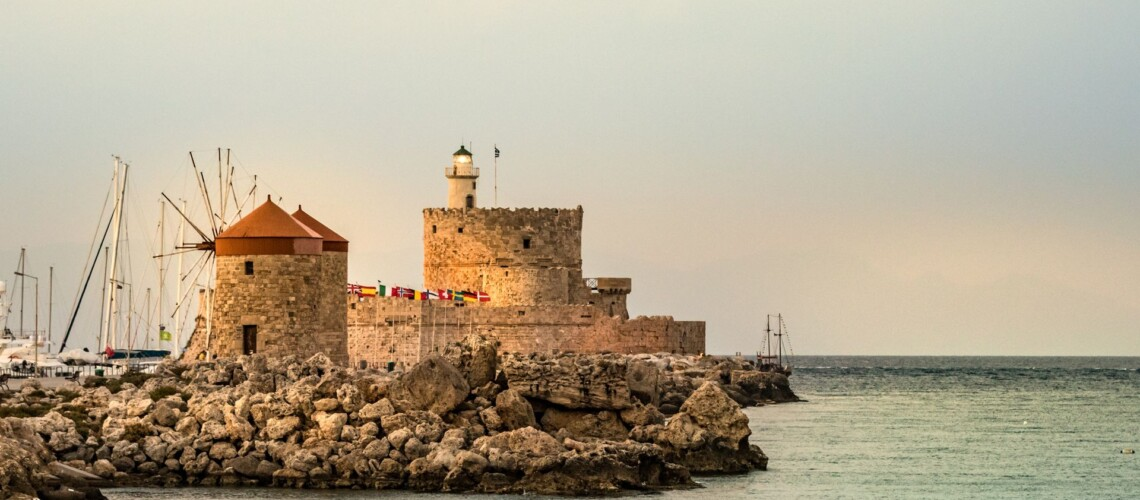 Windmills And The Lighthouse At Mandraki Harbour, Rhodes, Greece